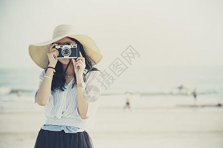 夕阳下海边拍照女孩背景图片