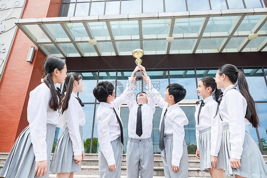 小学生团体手捧奖杯图片