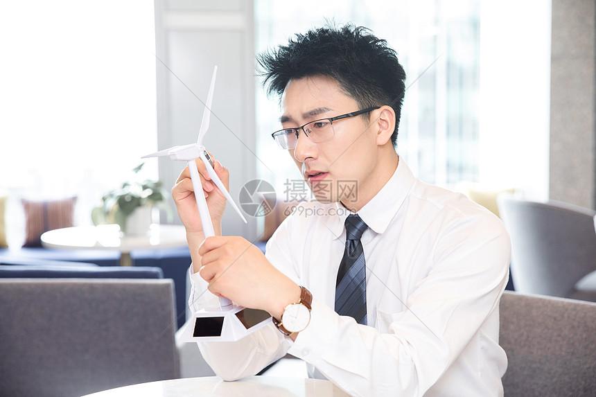 商务男士研究风车模型图片