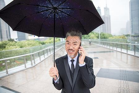商务男士撑伞打电话图片