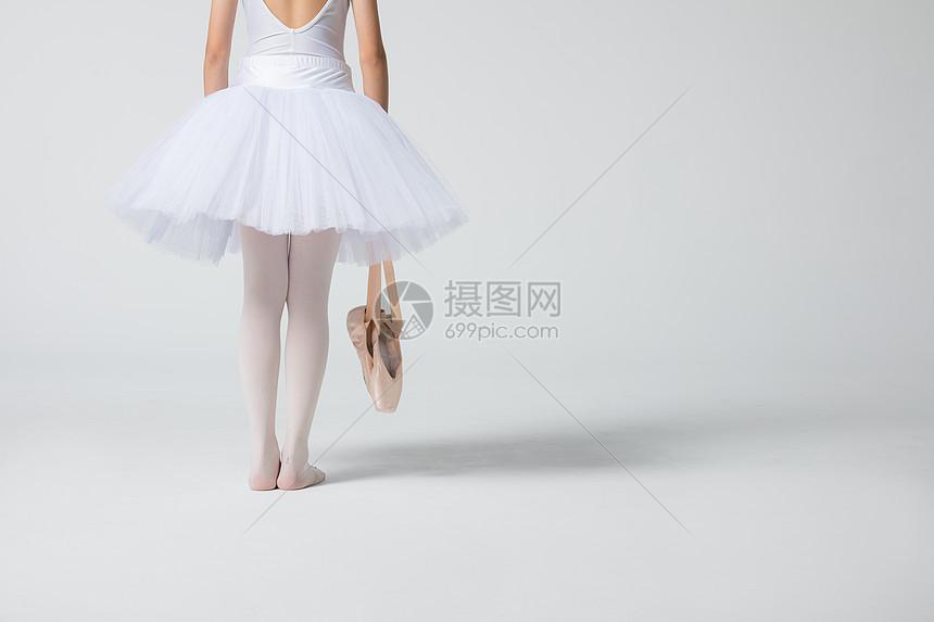 小女孩拎着舞鞋特写图片