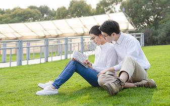 青年情侣坐在公园草地上看书图片