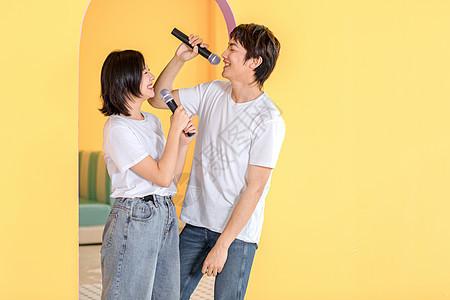 年轻情侣手持麦克风唱歌图片