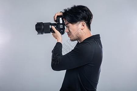 摄影师持相机拍照图片