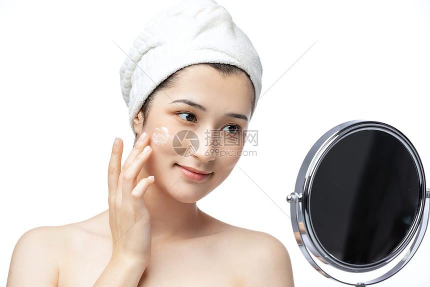 美女照镜子涂抹乳液图片