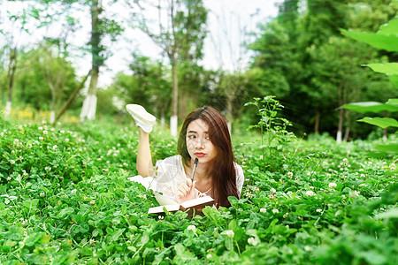 躺在草坪写作的女生图片