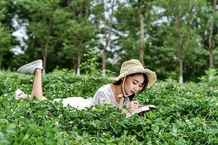 带着帽子躺着写字的女生图片