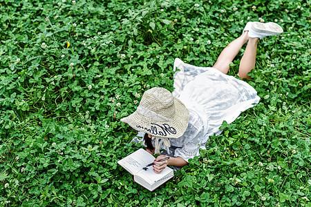 草坪上趴着看书的美女图片