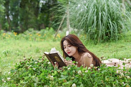 趴在花丛中看书的美女图片