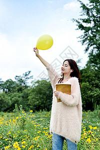 抱着书本手拿气球的女生图片