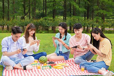 大学生野餐玩手机游戏图片
