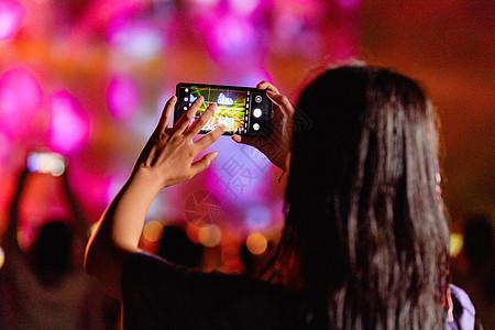潮流美女用手机在音乐节拍照图片