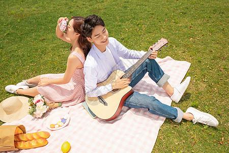 青年情侣郊游弹吉他图片