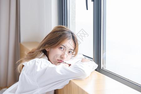 年轻女性靠在窗边图片