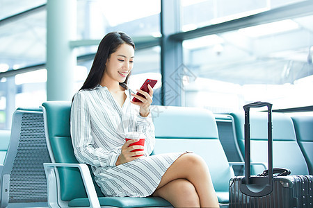 商务女士机场候车玩手机图片