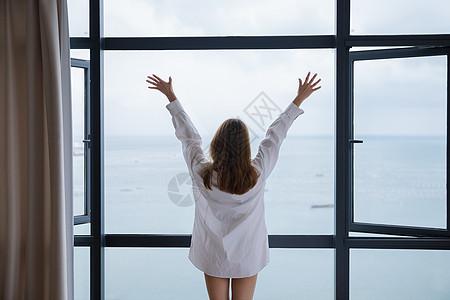 年轻女性窗边伸展背影图片