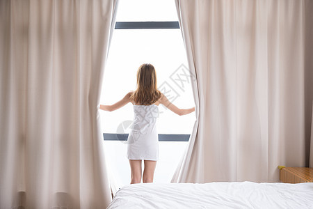 年轻女性起床拉窗帘背影图片