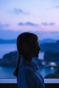 夏日黄昏美女窗边剪影图片