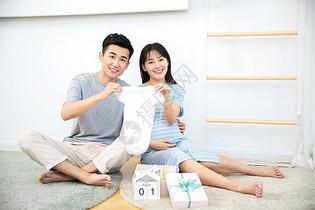 丈夫给孕妇展示自己给孩子买的婴儿衣服图片