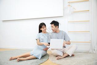 孕妇和丈夫一起在卧室地毯上看电脑图片
