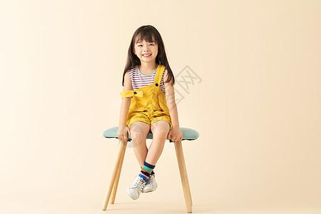 可爱小女孩乖巧坐在椅子上图片