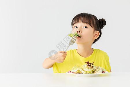 小女孩开心的吃着蔬菜沙拉图片