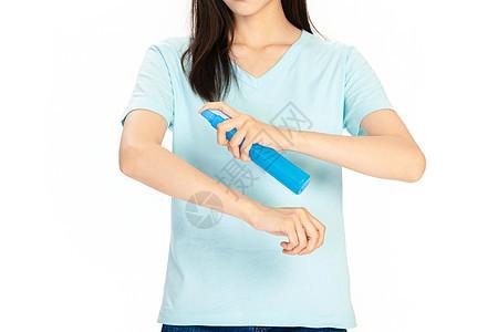 蓝色短袖美女在胳膊上用花露水图片