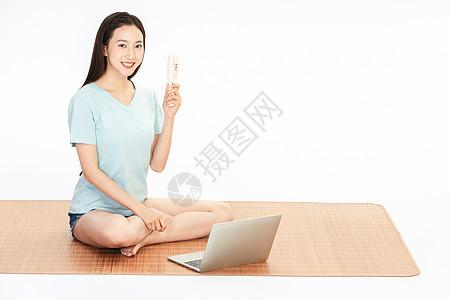 女生坐在凉席上吹小风扇图片