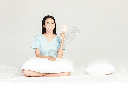 女性坐在床上吹小风扇图片