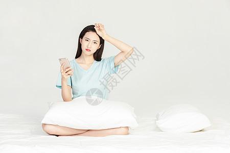 女性坐在床上玩手机图片