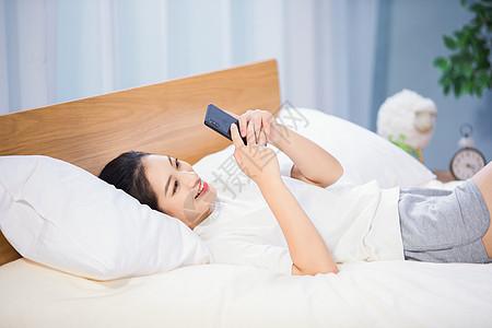 女性躺在床上玩手机图片