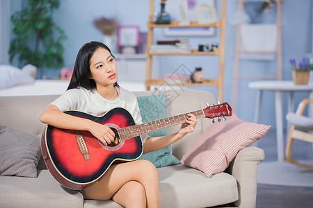 女性客厅弹吉他图片