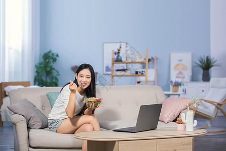 女性坐在沙发上吃东西图片
