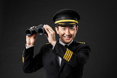 戴帽子的飞行员机长手拿望远镜图片