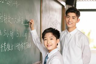 老师和学生微笑着在黑板上做题图片