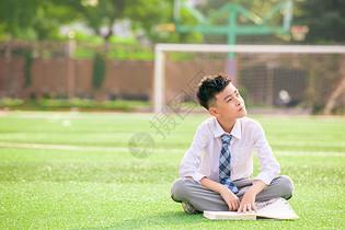 学生坐在操场上思考图片