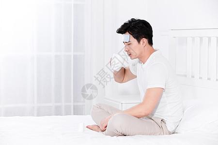 男子发烧坐在床上喝水吃药图片