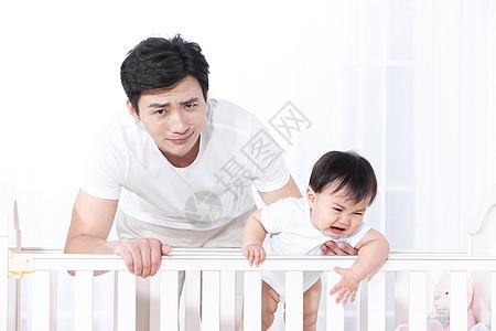 爸爸哄婴儿床中的婴儿图片