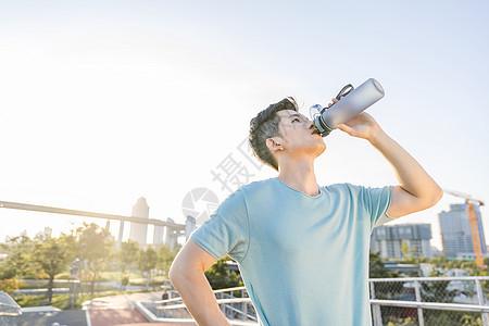 男性户外运动间隙喝水图片