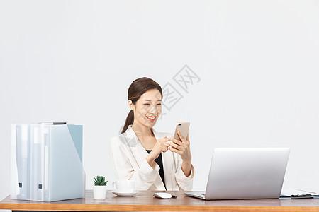 坐在办公室看手机的女性图片