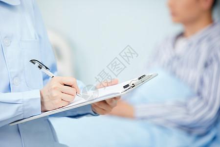 护士记录病人身体状况手部特写图片