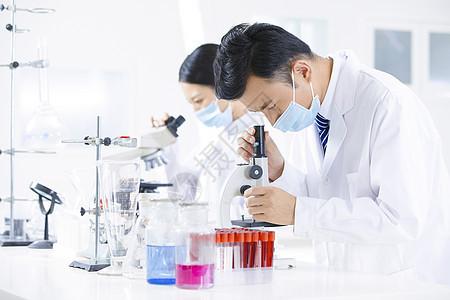 医疗研究人员用显微镜观察图片