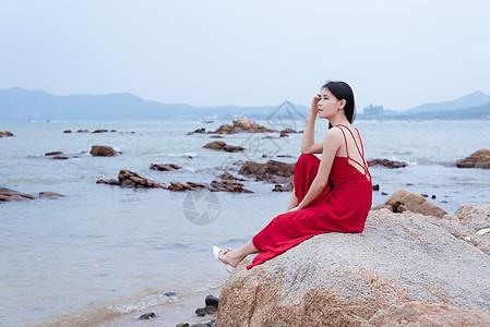 深圳较场尾海边礁石上的红衣少女侧影图片