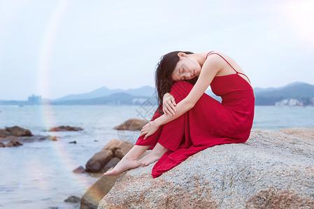 坐在深圳较场尾海边礁石上的红衣少女图片