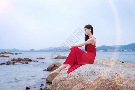 深圳较场尾海边礁石上的红衣少女图片