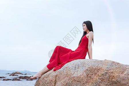坐在深圳较场尾海边礁石上的红裙子少女图片