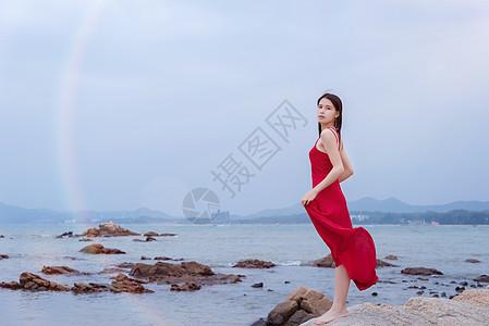 深圳较场尾海边礁石上的红衣少女手拿裙摆图片