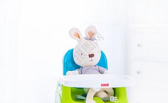 可爱的玩具兔坐在婴儿椅上图片