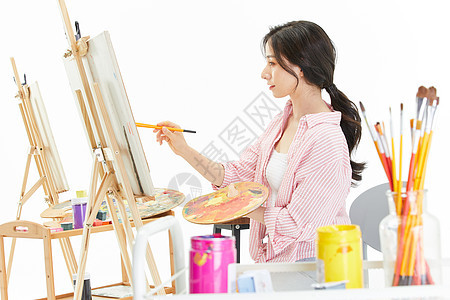 美女画家认真绘画侧面图片