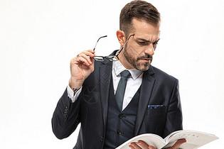 外国商务男性手拿眼镜看书特写图片
